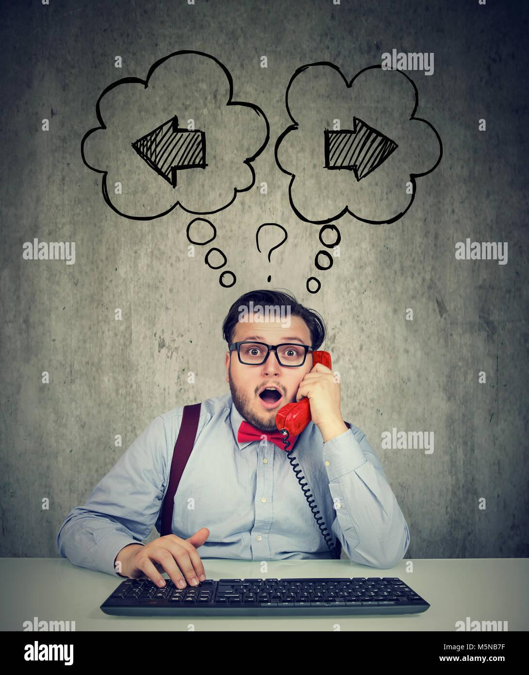 Imprenditore con tastiera a parlare su un telefono incerto sulla prossima fase di business Immagini Stock
