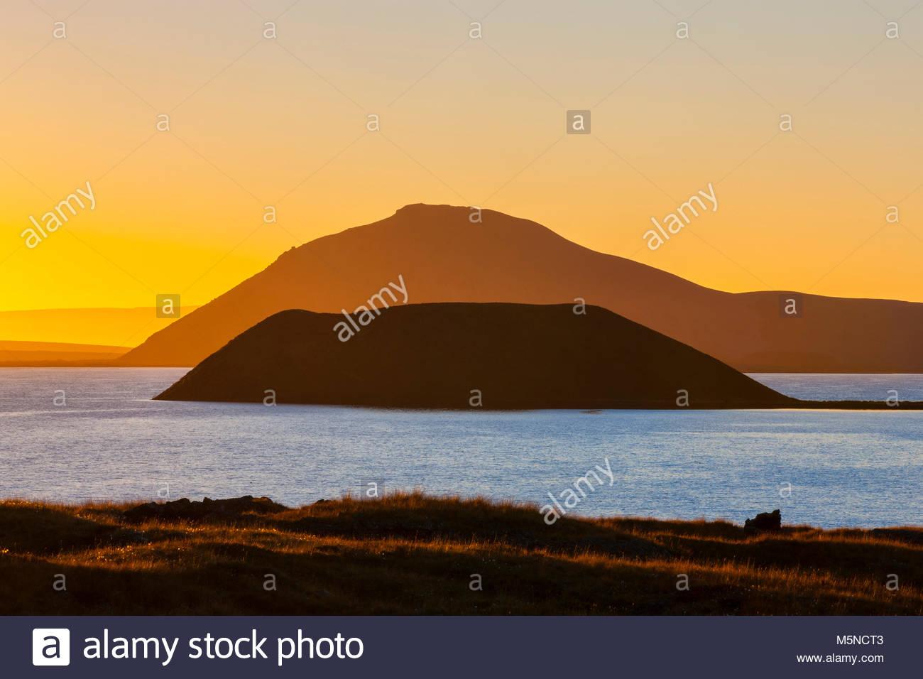 Un pseudocrater è reso in silhouette contro un cono volanic al tramonto in Mývatn nel nord dell'Islanda. Immagini Stock