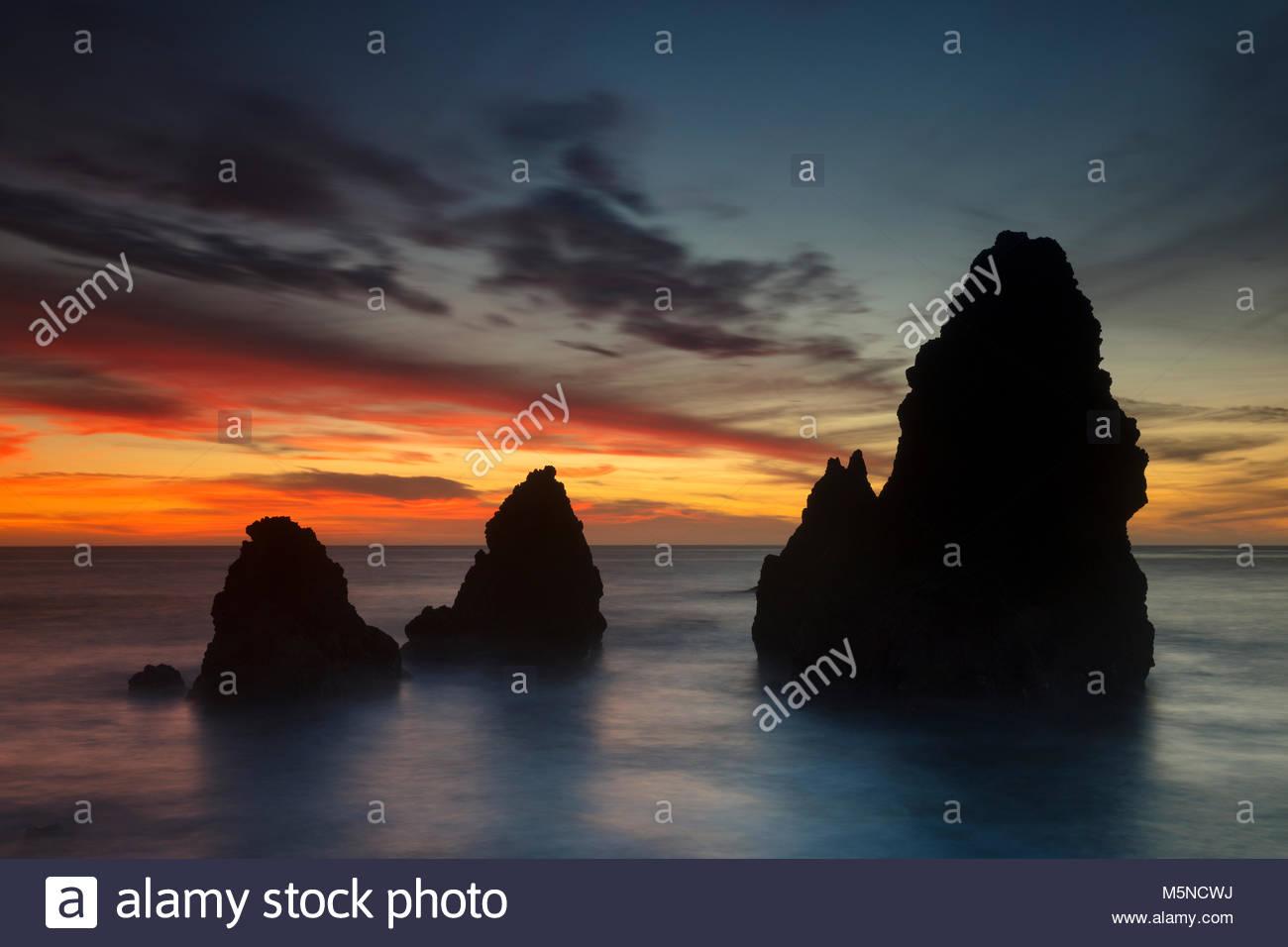 Un drammatico tramonto colora il cielo dietro il grande mare di pile in Rodeo Cove si trova nel Marin Headlands Immagini Stock