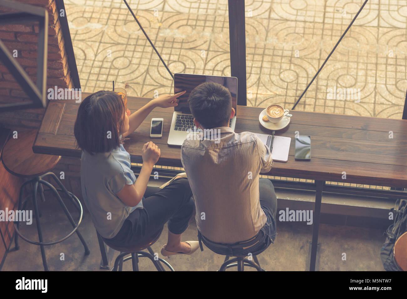 Punto di donna al laptop e discutere con i partner Immagini Stock
