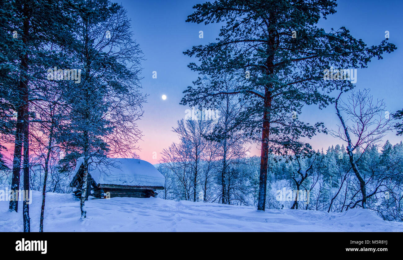 Vista panoramica della splendida winter wonderland paesaggi con tradizionale rifugio di legno in scenic luce della sera al tramonto in Scandinavia, Nord Euro Foto Stock