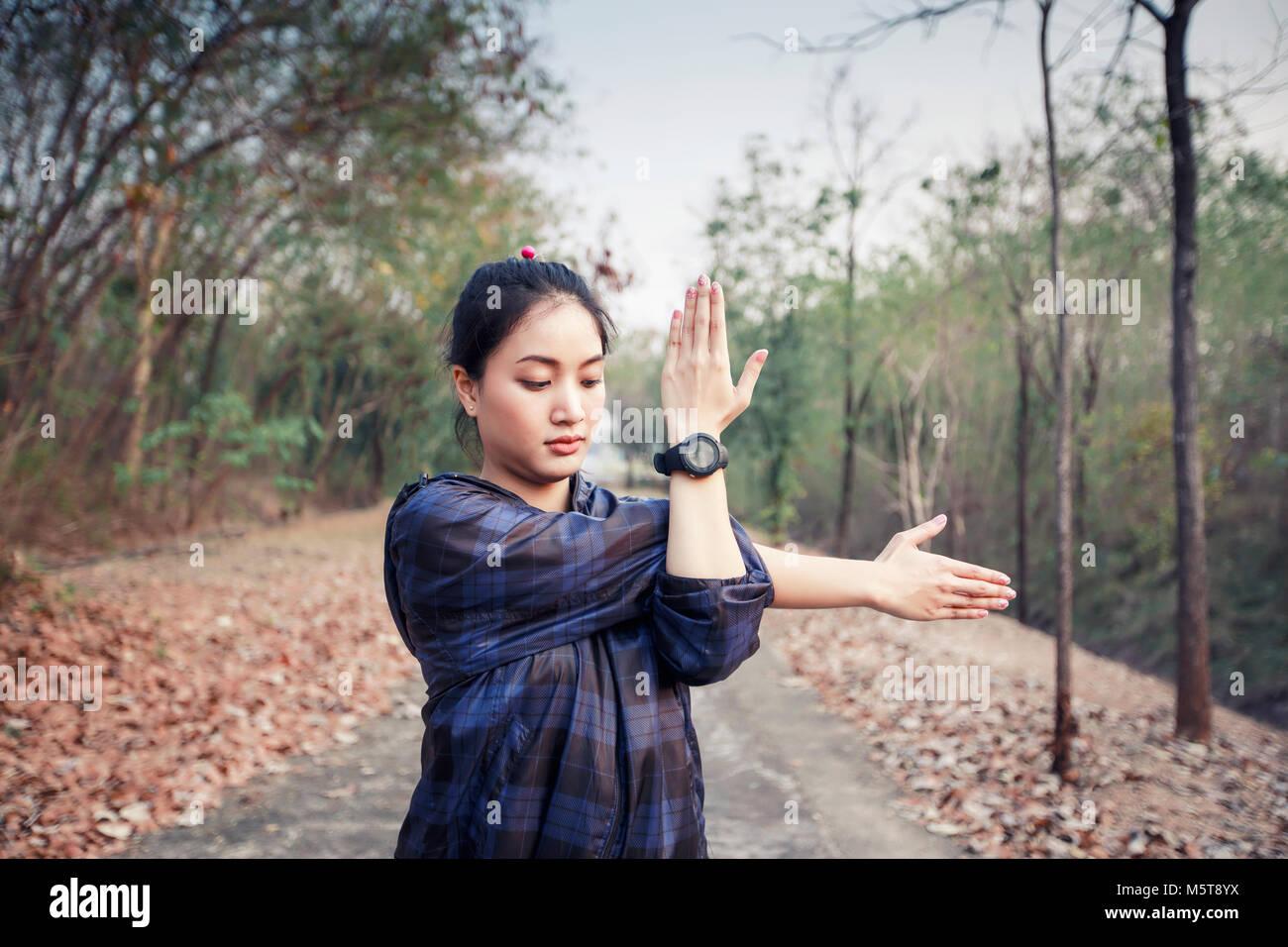Athletic donna asia il riscaldamento e il giovane atleta femminile esercizio e stiratura in un parco prima di Runner Immagini Stock