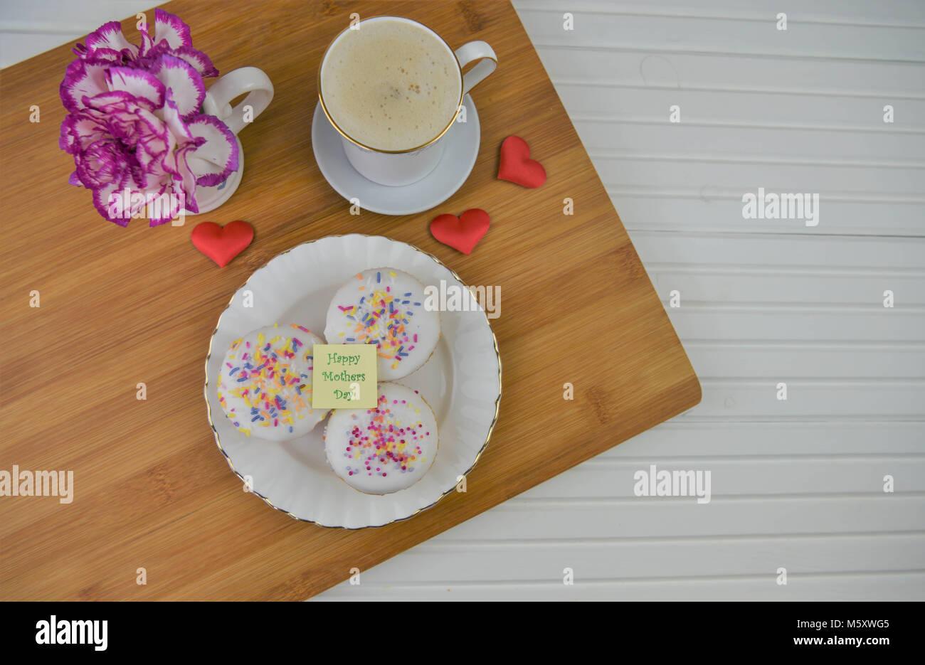 Felice Festa della mamma parole con cibo fatto in casa di mini Iced Cakes e fiori freschi Immagini Stock