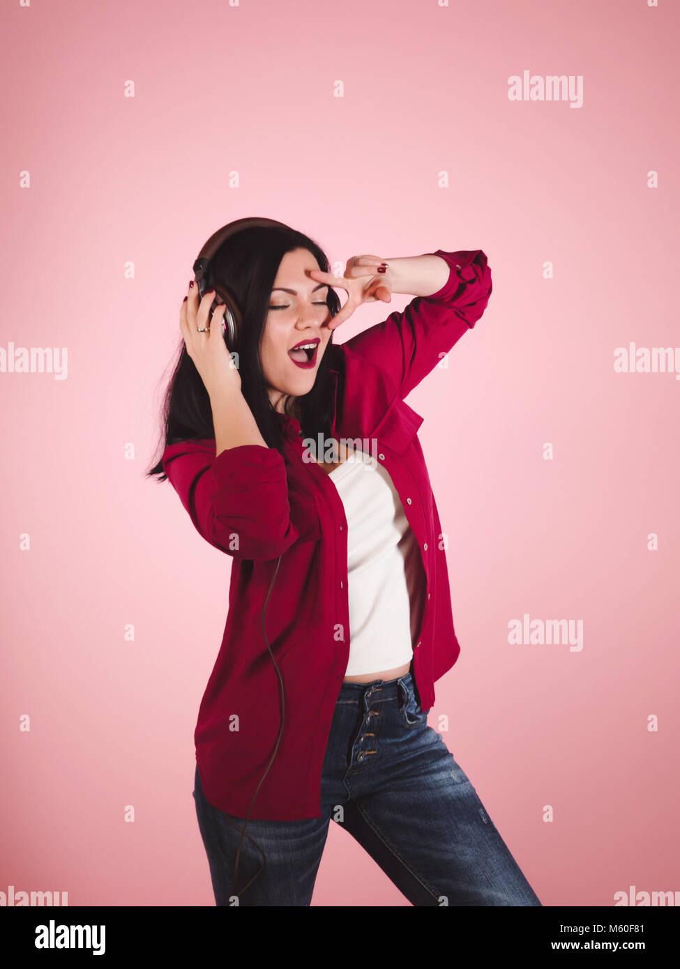 La gioia e la musica. Studio colorato ritratto di felice bruna giovane  donna con gli auricolari è ballare e cantare su sfondo rosa. 2b06c3a33baa