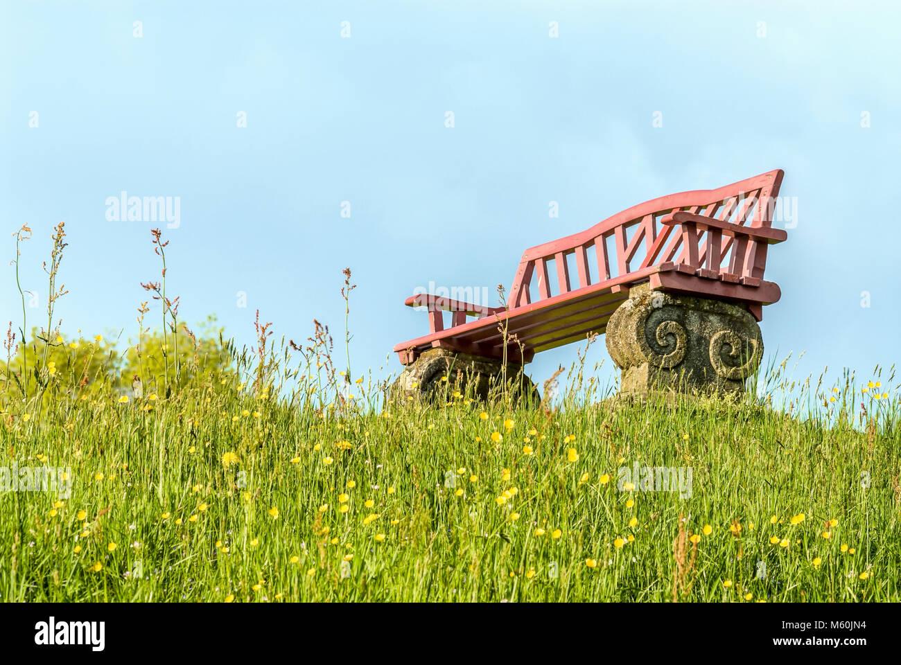 Panchina da giardino su un verde prato primavera collina con fiori visti dal di sotto, Svizzera Immagini Stock