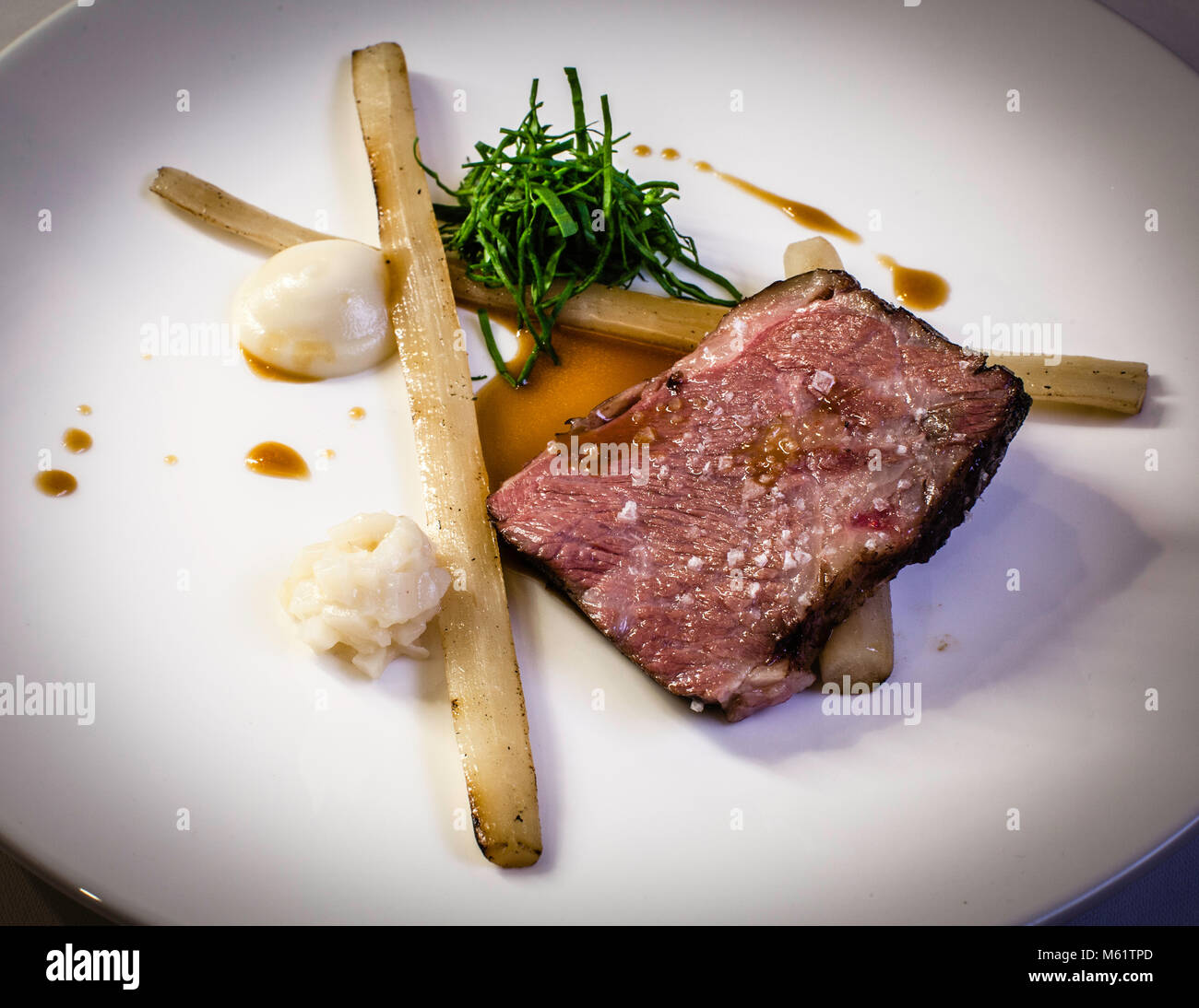Petto di manzo alla griglia con salsa e radice di girasole di Michelin Lo chef Marco Müller Foto Stock