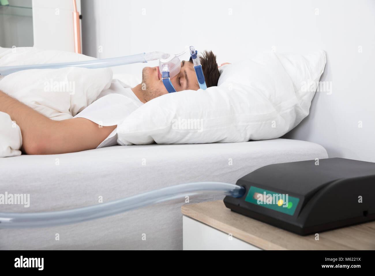 Giovane uomo disteso sul letto con apnea nel sonno e CPAP Immagini Stock