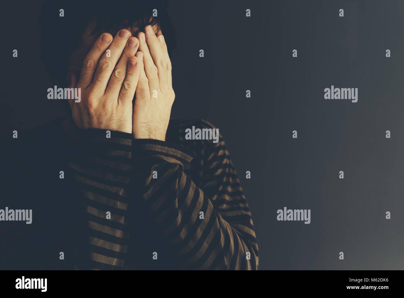 Uomo disperato di piangere da soli, chiave di basso verticale con il fuoco selettivo Foto Stock