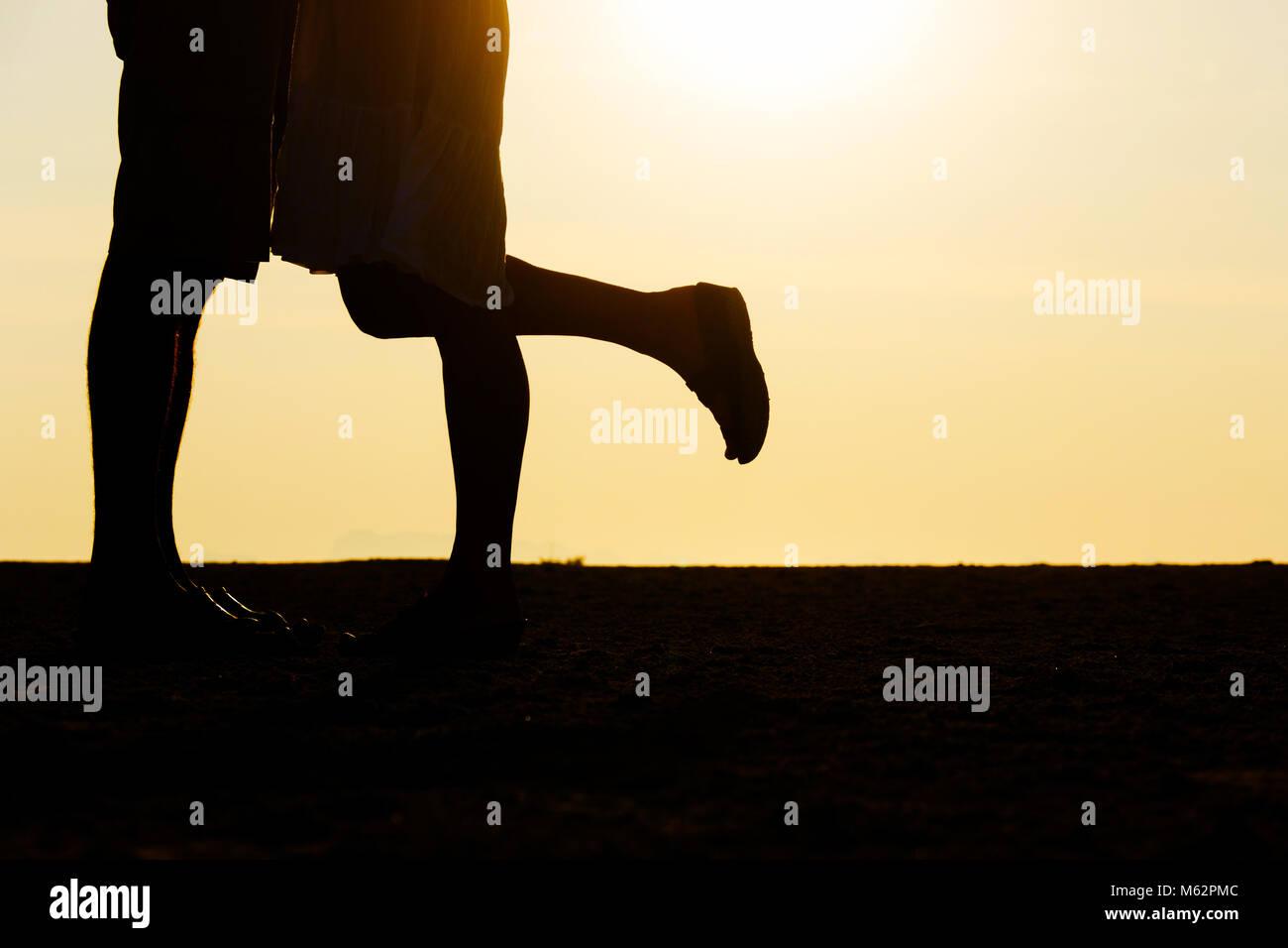 Silhouette di giovane kissing al tramonto sul mare con una delle sue gambe sollevata. Classico film romantico momento Immagini Stock
