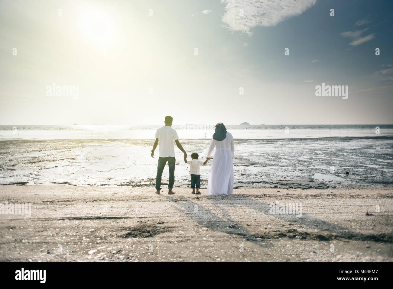 La famiglia felice avente tempo di divertimento insieme alla spiaggia con bella vista al tramonto si trova a Pantai Immagini Stock