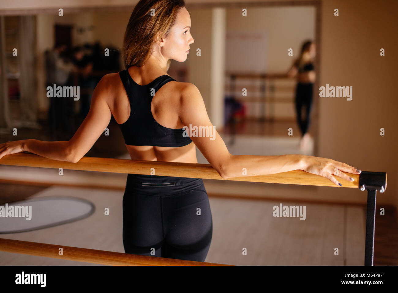 Donna ballerina in posa vicino a barre nel balletto studio. Immagini Stock