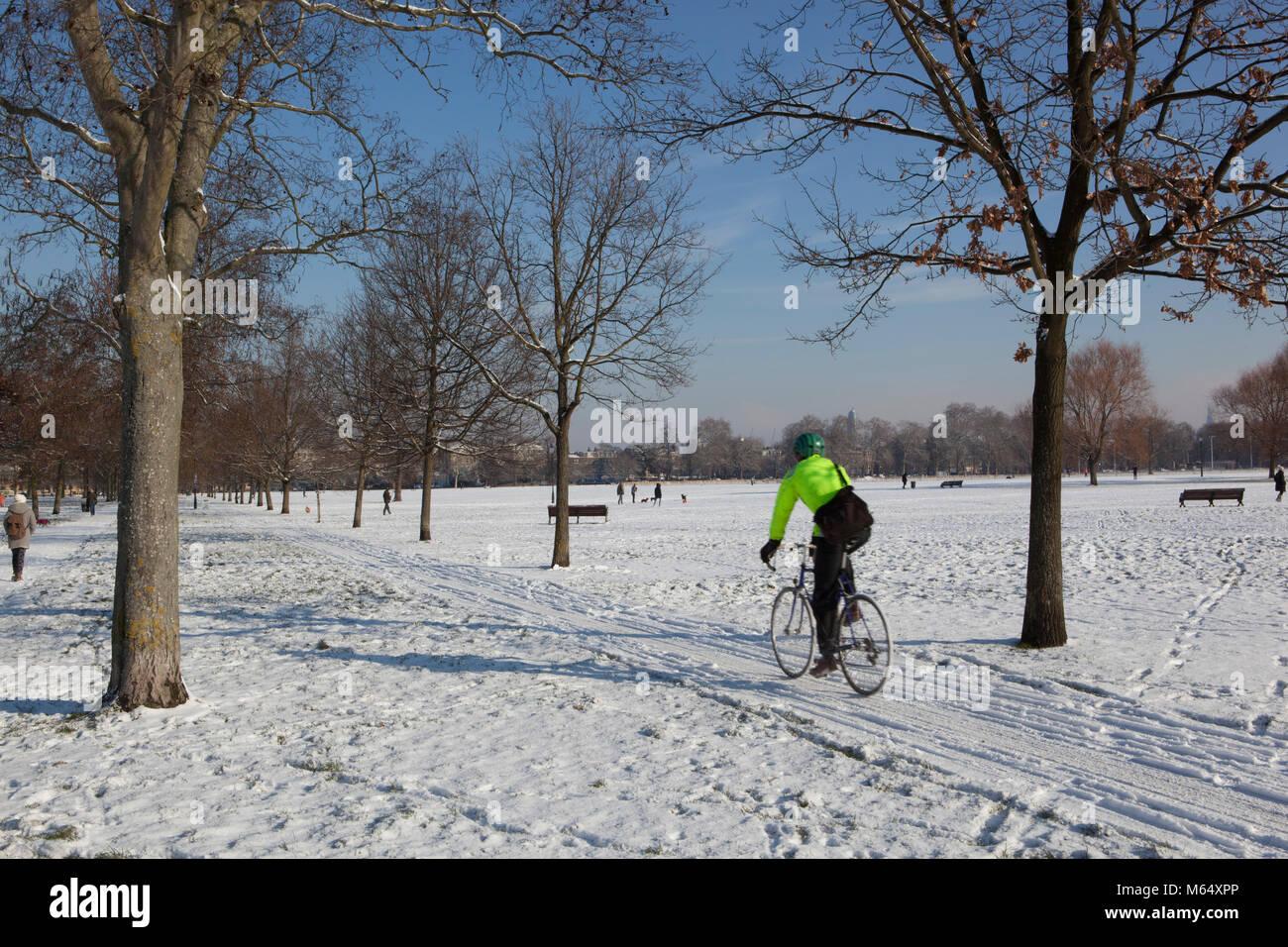 Un ciclista pedalando attraverso la neve sulla Clapham Common Immagini Stock