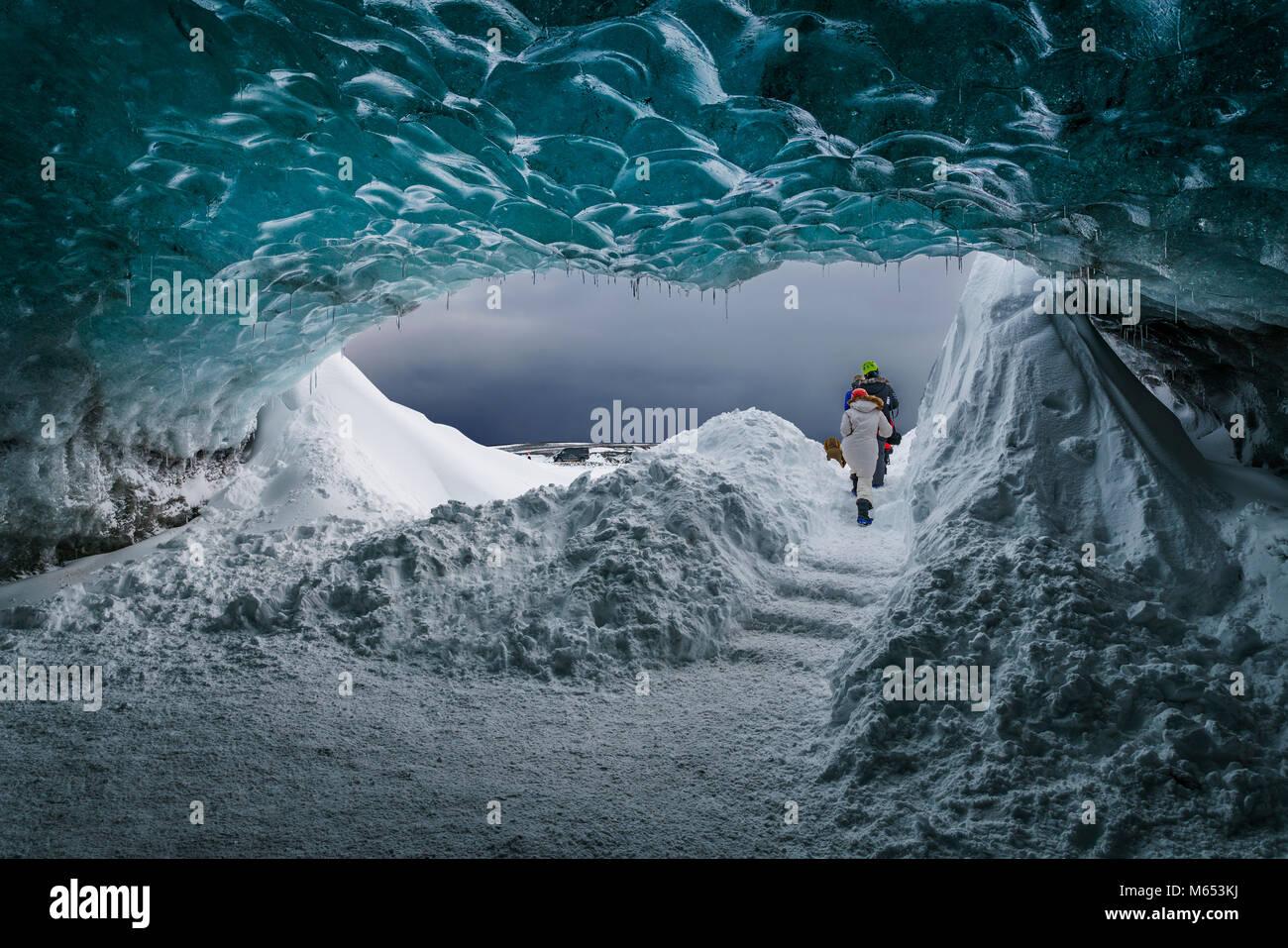 I turisti nella Grotta dei Cristalli, Breidamerkurjokull Glacier, Islanda. Emerald Blue Ice e ceneri è parte Immagini Stock