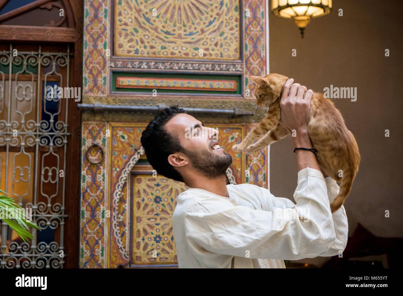 Giovani Musulmani uomo in abbigliamento tradizionale tenendo un gatto giallo in un tradizionale ambiente Marocchino Immagini Stock