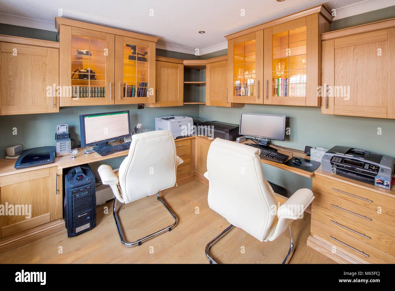 Home office o di uno studio che mostra mobili, scrivanie, computer, stampanti e sedie Immagini Stock