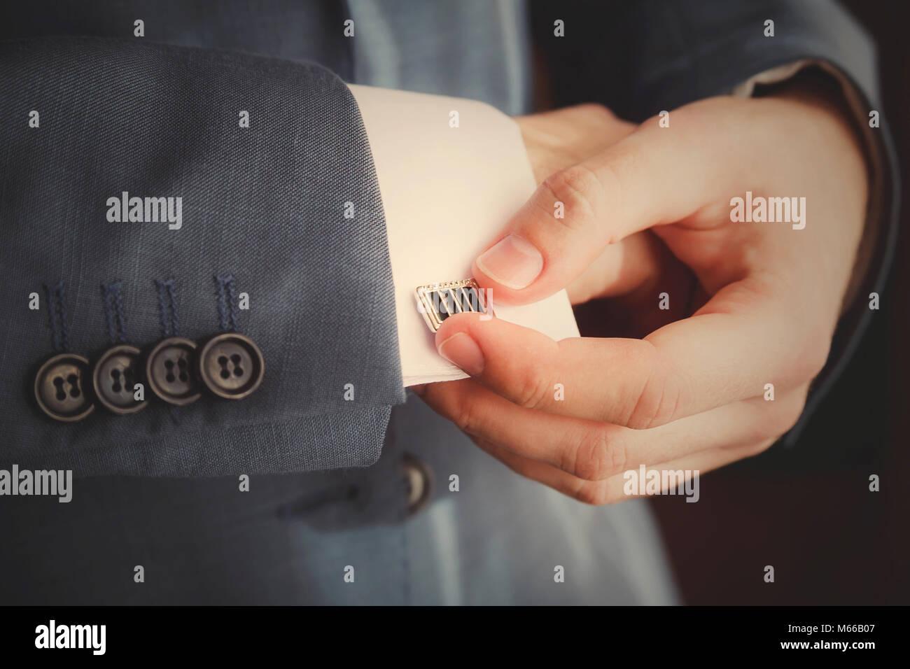Lo sposo mettendo sul bracciale-links come egli si veste di usura formale close up Immagini Stock