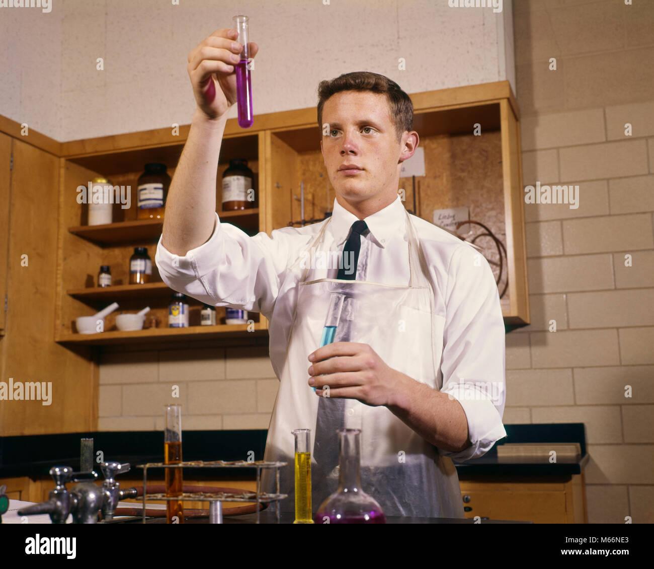 Anni sessanta maschio di alta scuola studente adolescente nel laboratorio di chimica AZIENDA PROVETTE - KS2094 HAR001 Immagini Stock