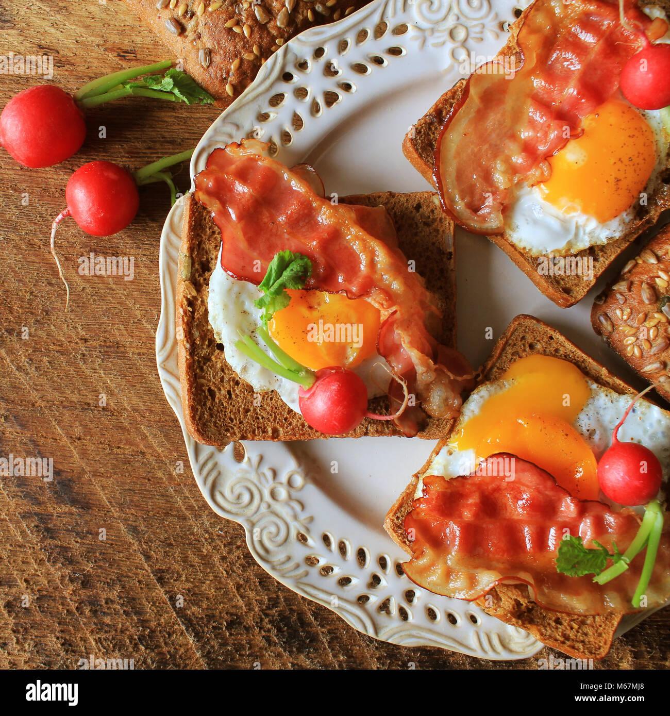 La prima colazione , bacon croccante, uova fritte e pane. Panini sulla piastra bianca. Tavolo rustico . Vista superiore Immagini Stock