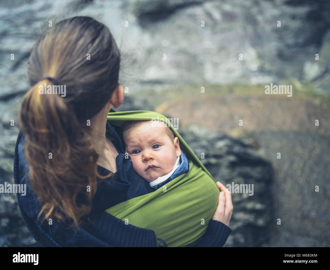 Una giovane madre è in piedi fuori in natura con il suo bambino in una imbracatura Immagini Stock