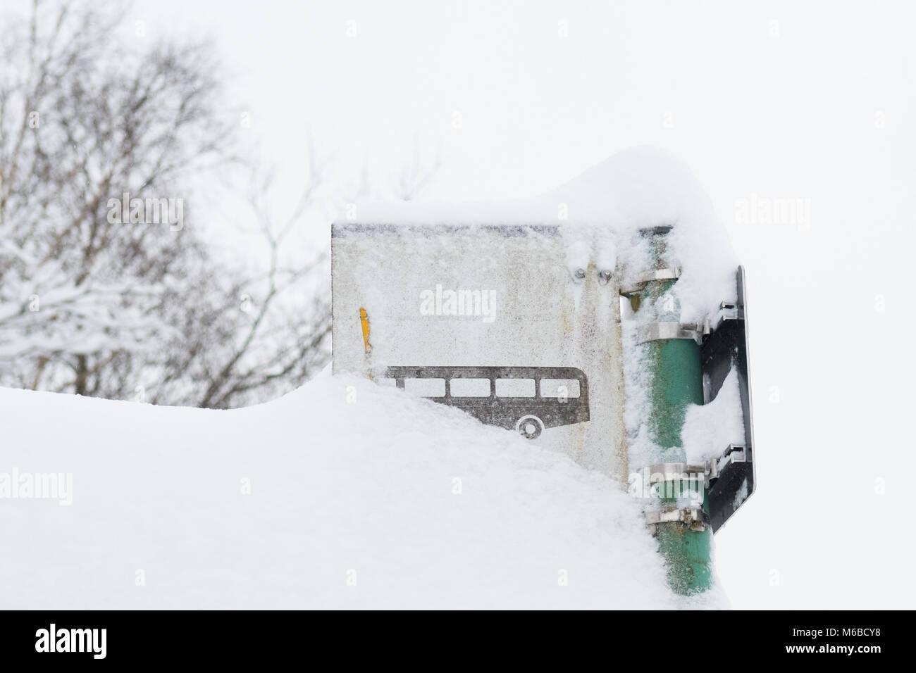 Fermata bus segno ricoperta di neve - trasporto pubblico nel concetto di inverno - Scozia, Regno Unito Immagini Stock