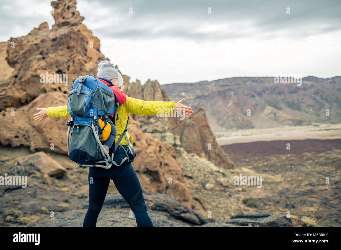 Super mom con baby boy in viaggio nello zaino. Avventura Trekking con bambino in autunno viaggio con la famiglia Immagini Stock