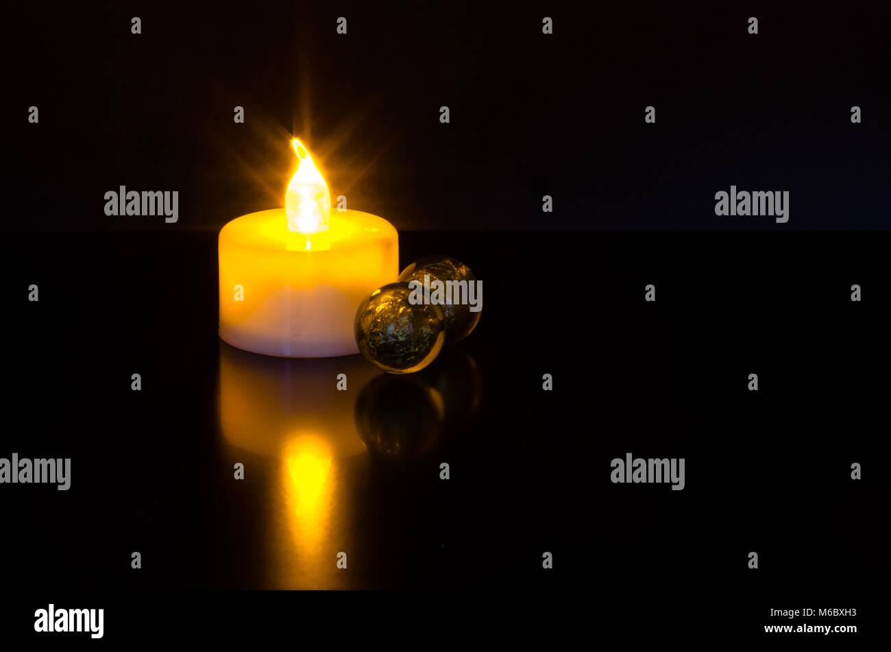 Led di candela luce riflessione scintillanti e marmo verde palle su sfondo nero Immagini Stock