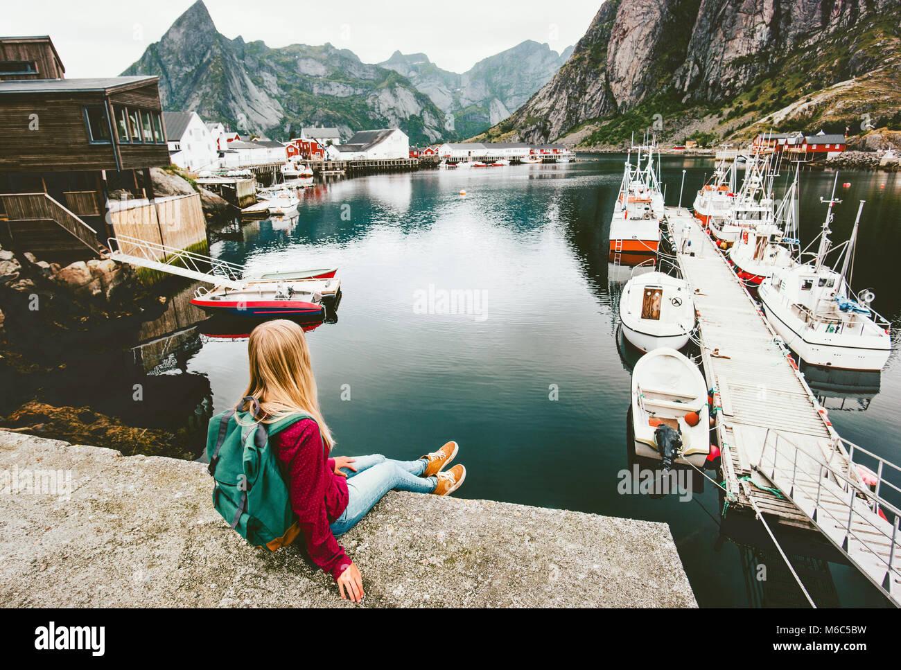 Giovane donna rilassante turistica sul ponte sul fiordo in isole Lofoten di Norvegia viaggiare con lo zaino in spalla Immagini Stock