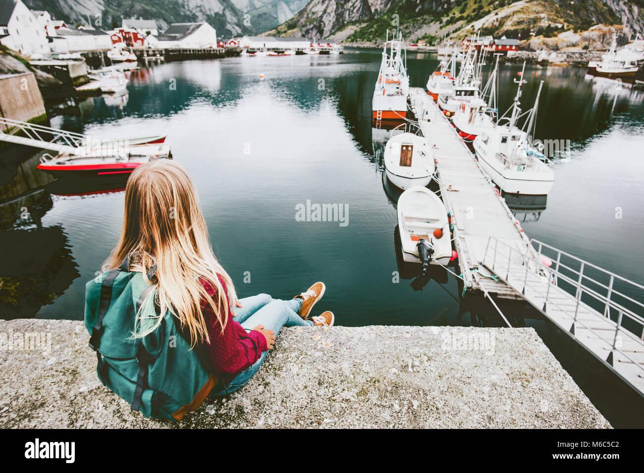 Donna bionda con zaino rilassante sul ponte sul mare con barche Visualizza stile di vita viaggio avventura concetto Immagini Stock