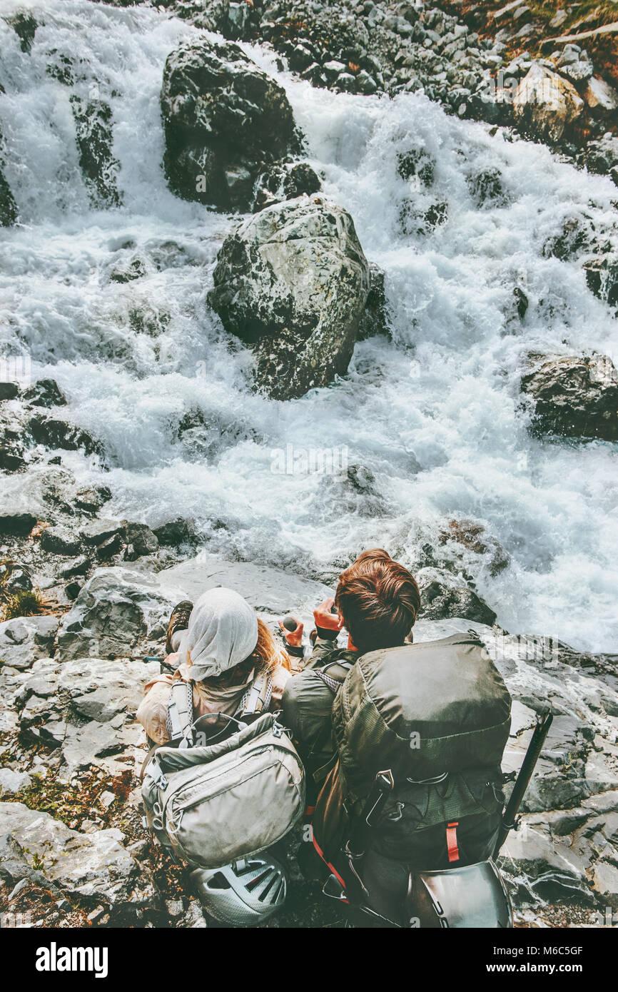 Giovane avventurieri rilassante nel fiume di montagna insieme amore e stile di vita viaggio wanderlust concetto Immagini Stock