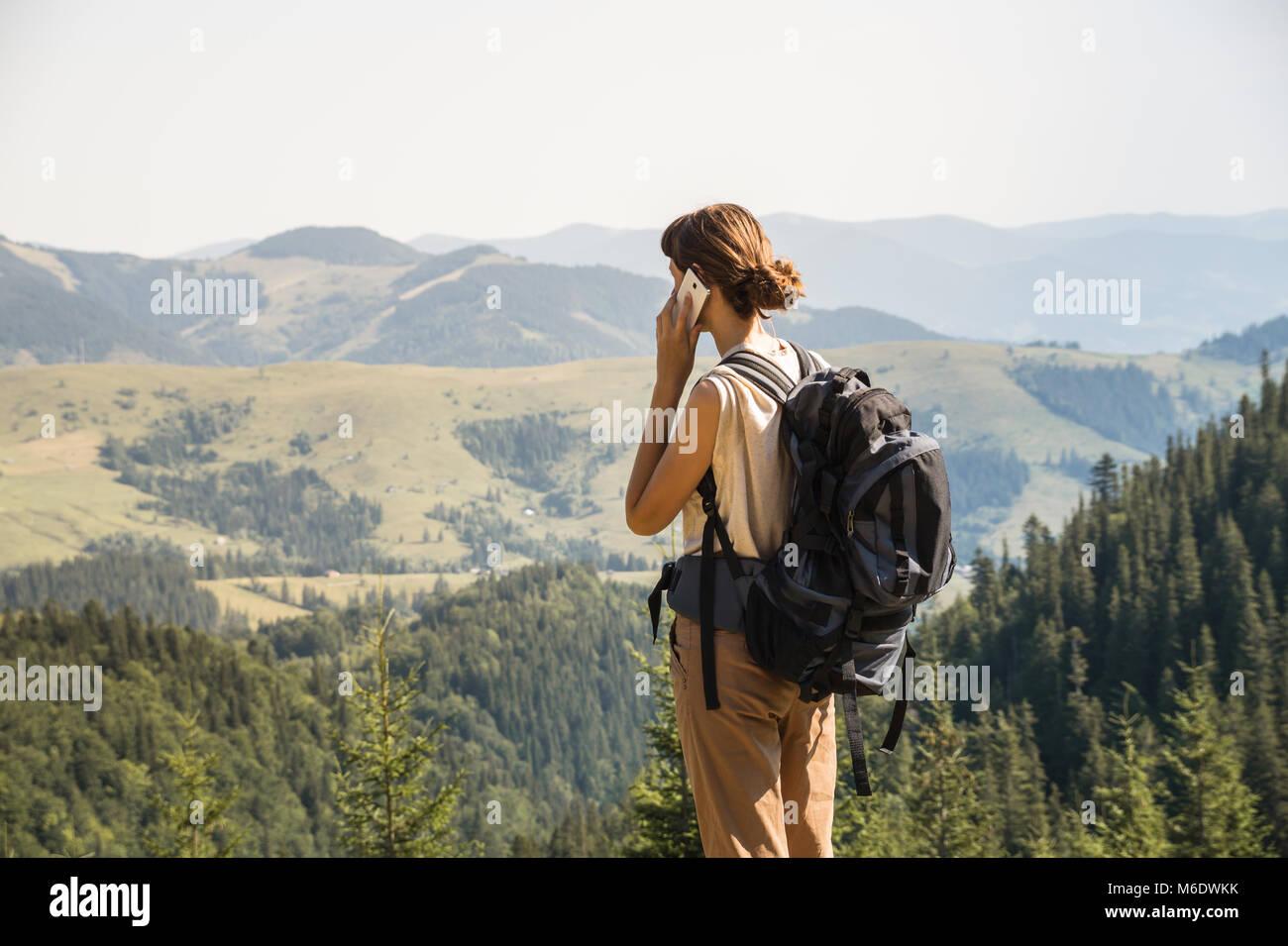 Ragazza con zaino turistico su una lunga escursione a piedi i colloqui sullo smartphone in collina Immagini Stock