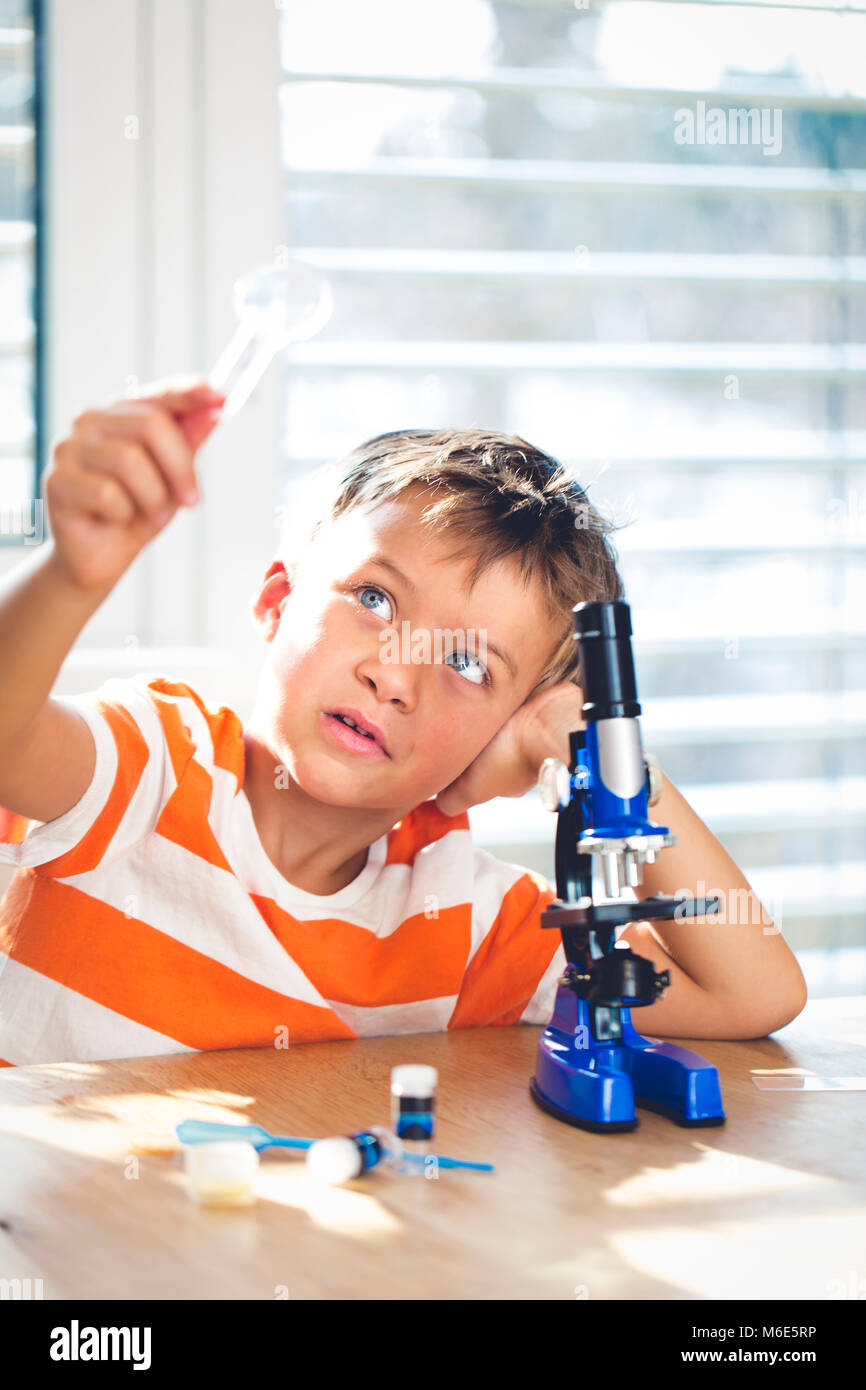 Giovane ragazzo è in possesso di una lente di ingrandimento in mano e si guarda attraverso Immagini Stock