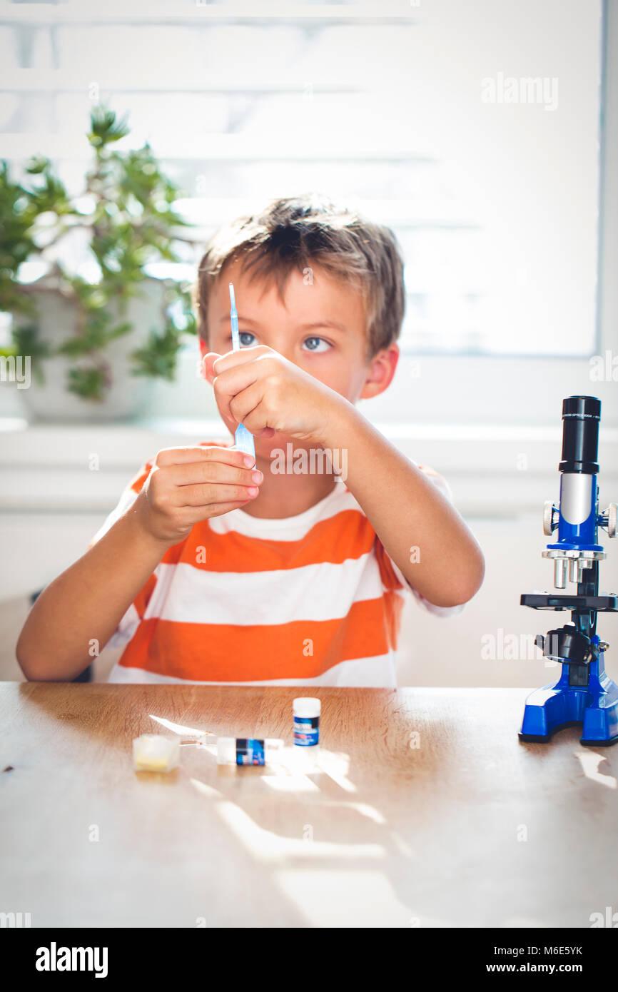Giovane ragazzo sta lavorando con il microscopio ed esamina le cose differenti Immagini Stock