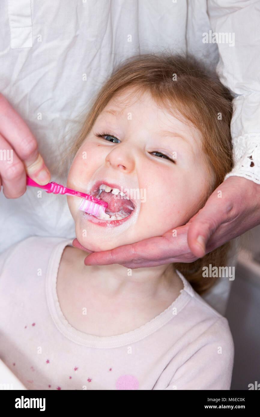 Tre anni di bambino / bambino di età compresa tra i 3 anni avente il suo latte denti spazzolati con uno spazzolino Immagini Stock