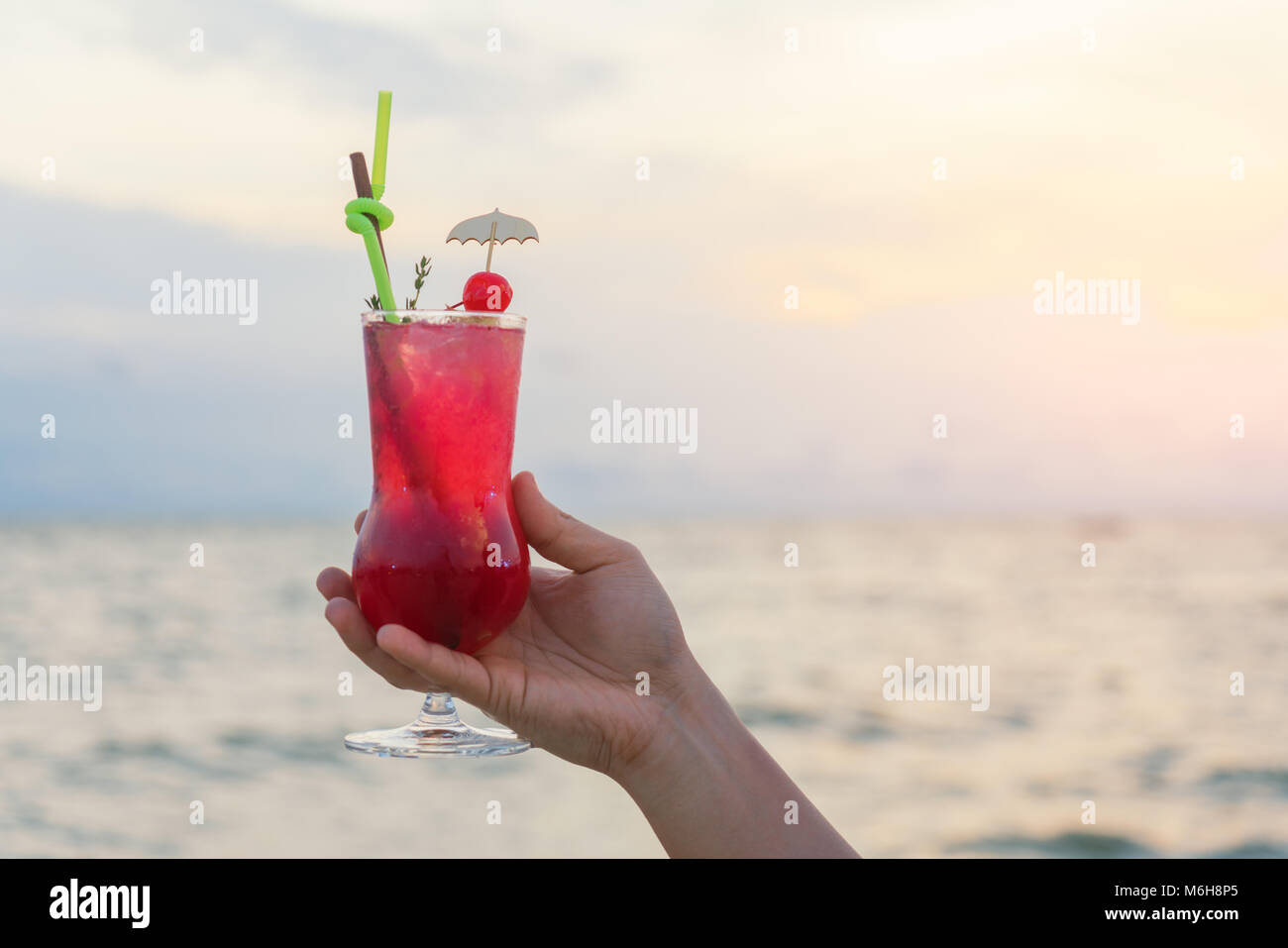 Mano azienda red cocktail drink in twilight sea & sky background. Estate, vacanze, viaggi e vacanze concetto. Immagini Stock
