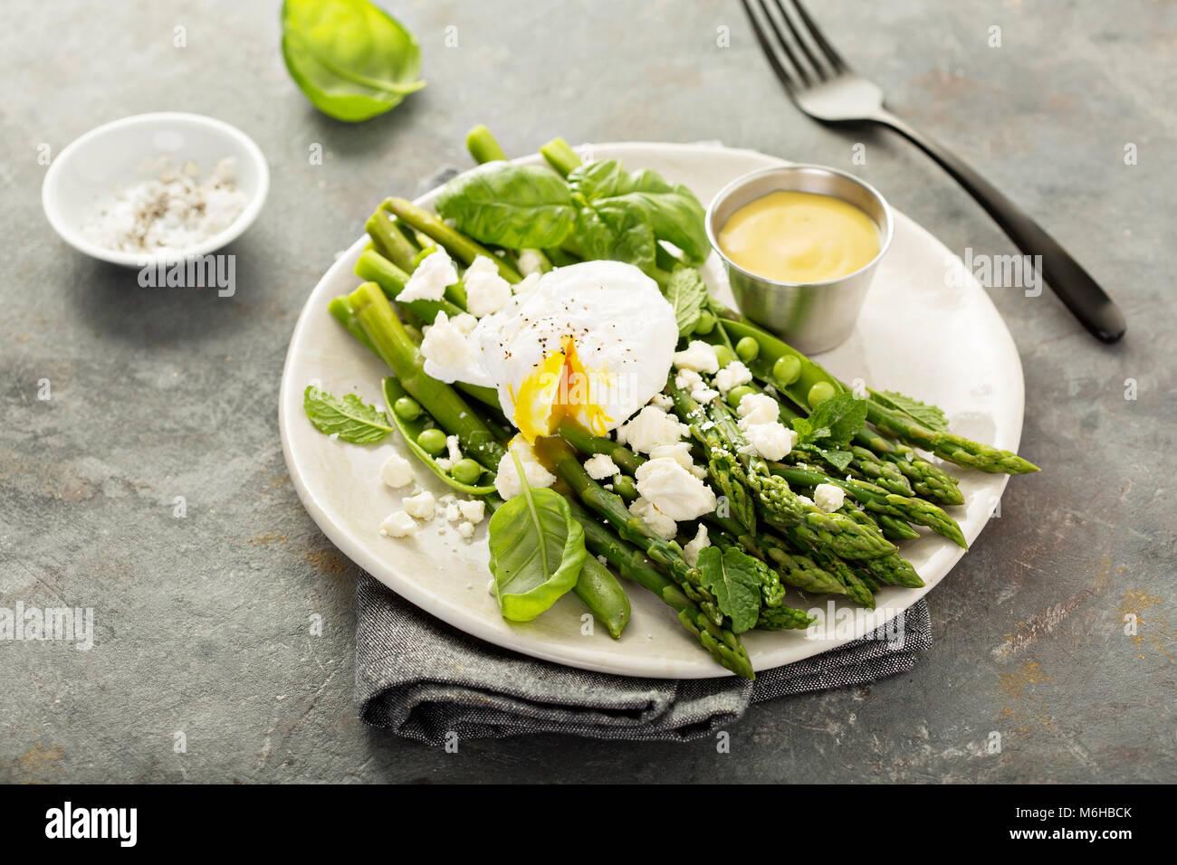 Piselli verdi e asparagi con uovo in camicia Immagini Stock