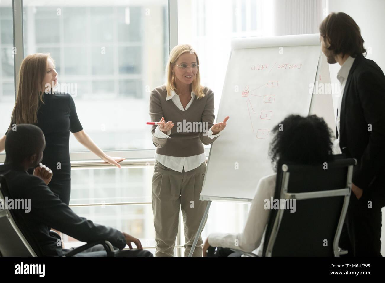 Femmina di team leader o business coach dando la presentazione a empl Immagini Stock