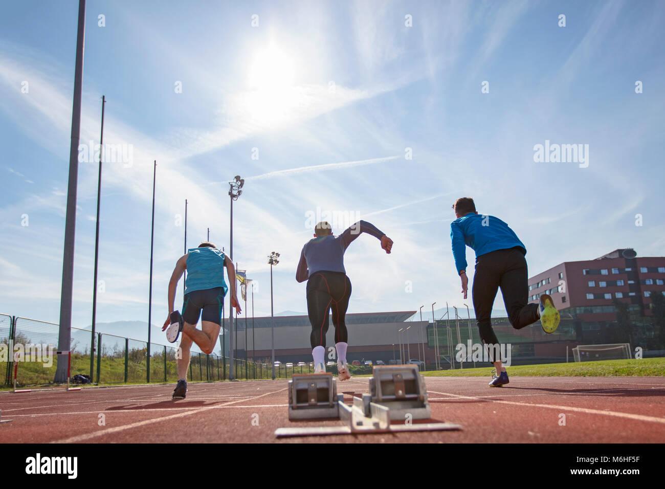 Gli atleti nello sprint la linea di partenza in pista e sul campo Immagini Stock
