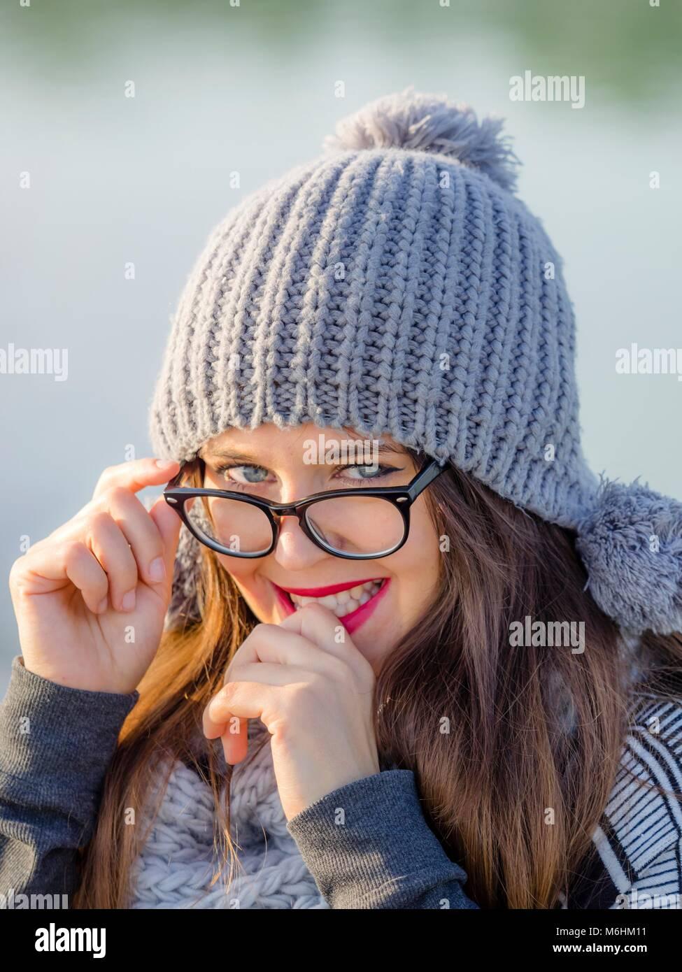 Piuttosto giovane donna ritratto con il grigio inverno cappello e occhiali Foto Stock