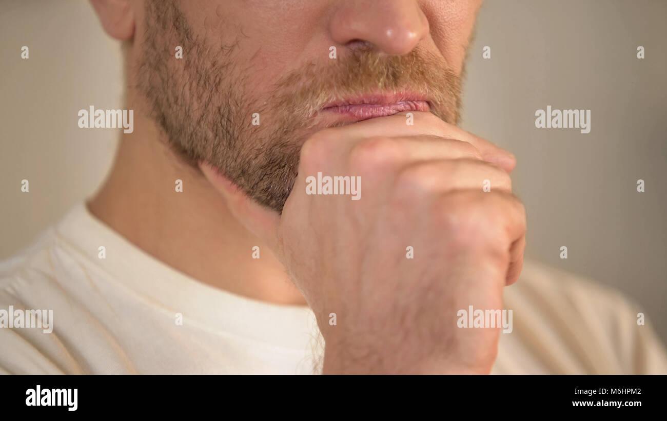 Close-up del giovane serio con la barba sfrega mento, avendo dubbi, pensando Immagini Stock