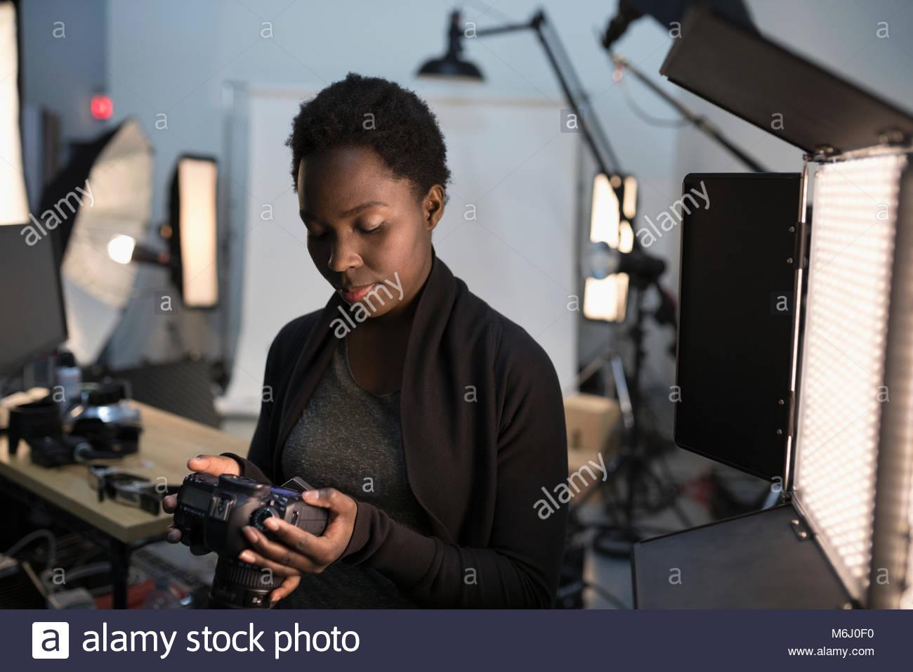 Fotografo femmina guardando la fotocamera digitale mirino al foto riprese in studio Immagini Stock