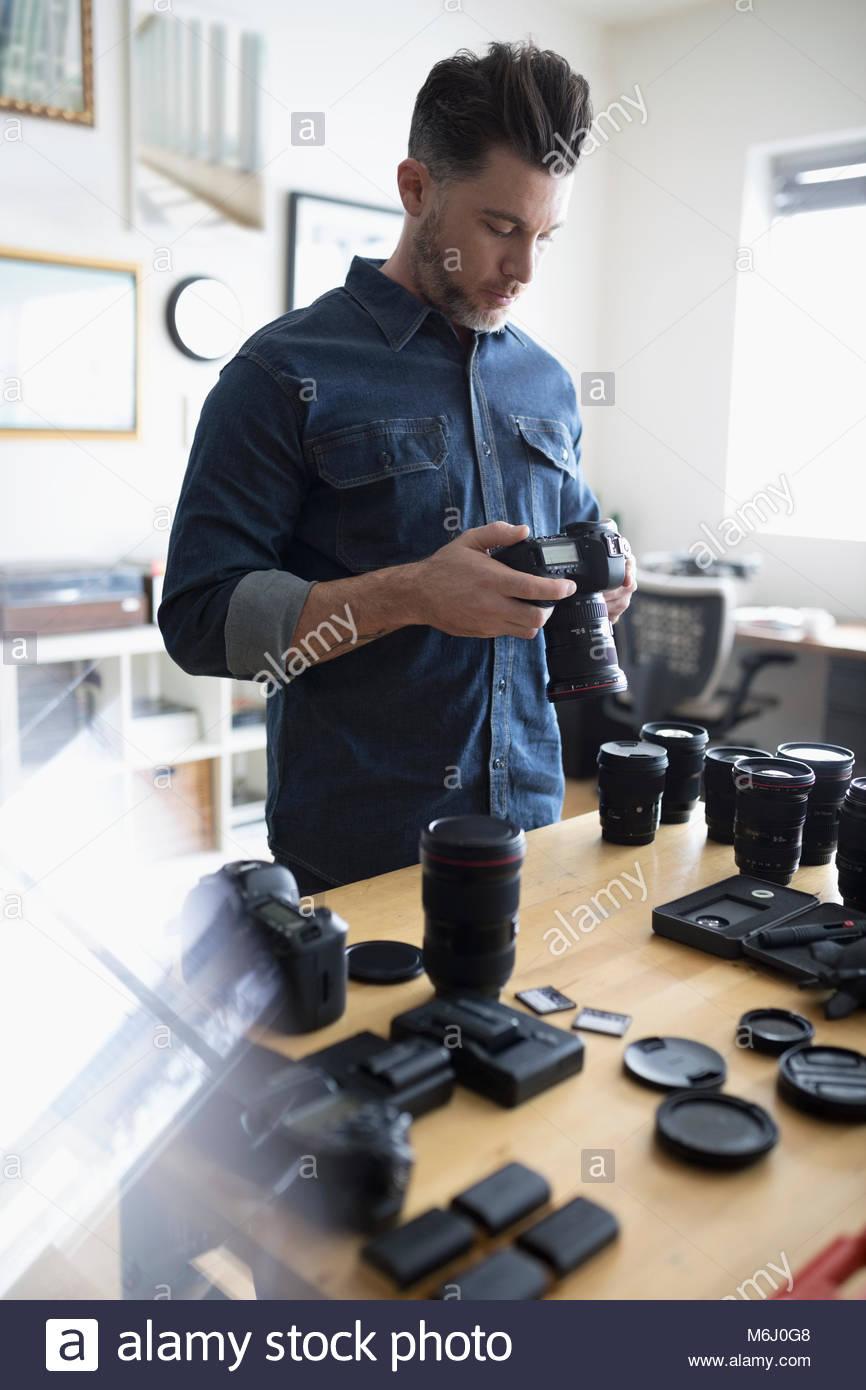 Fotografo maschio con la fotocamera digitale e le attrezzature Immagini Stock
