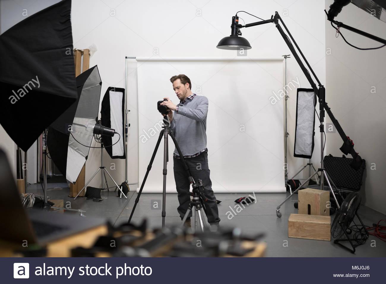 Fotografo maschio preparazione fotocamera digitale attrezzature per foto riprese in studio Immagini Stock