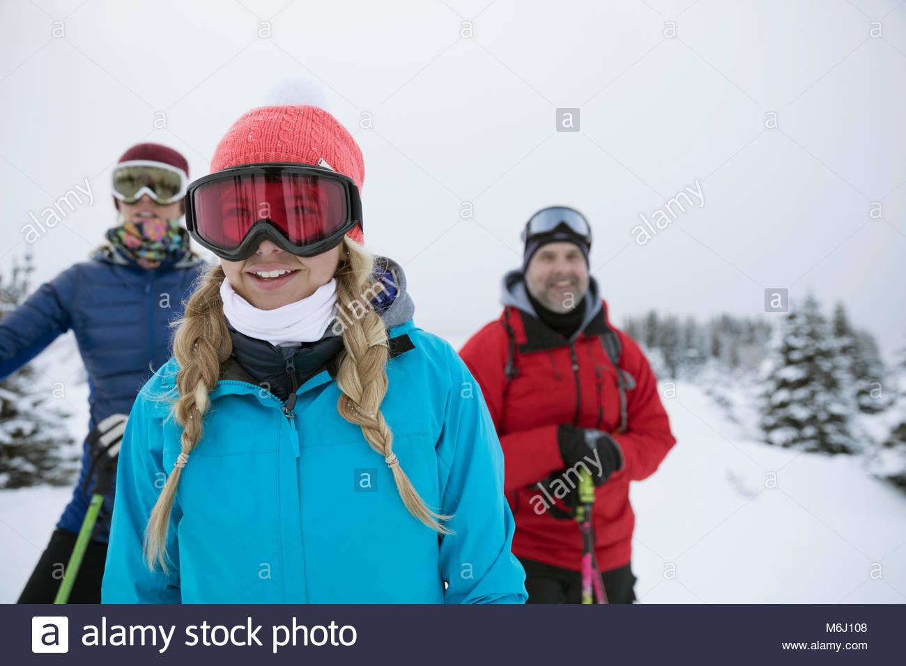 Ragazza felice di fare escursioni con le racchette da neve con la famiglia Immagini Stock