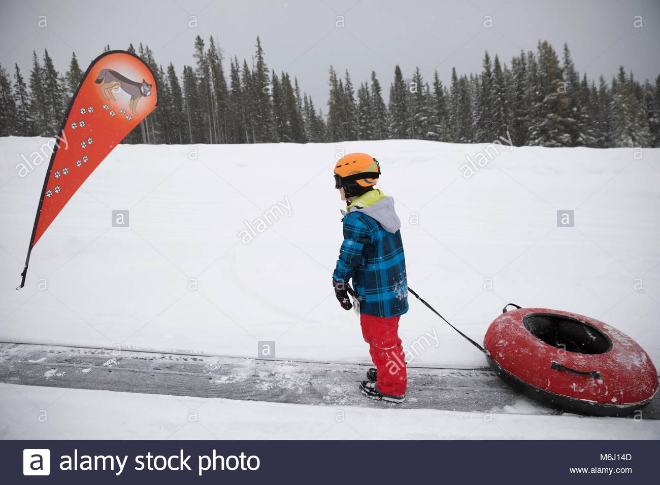 Ragazzo tirando il tubo interno nella neve a snow park Immagini Stock