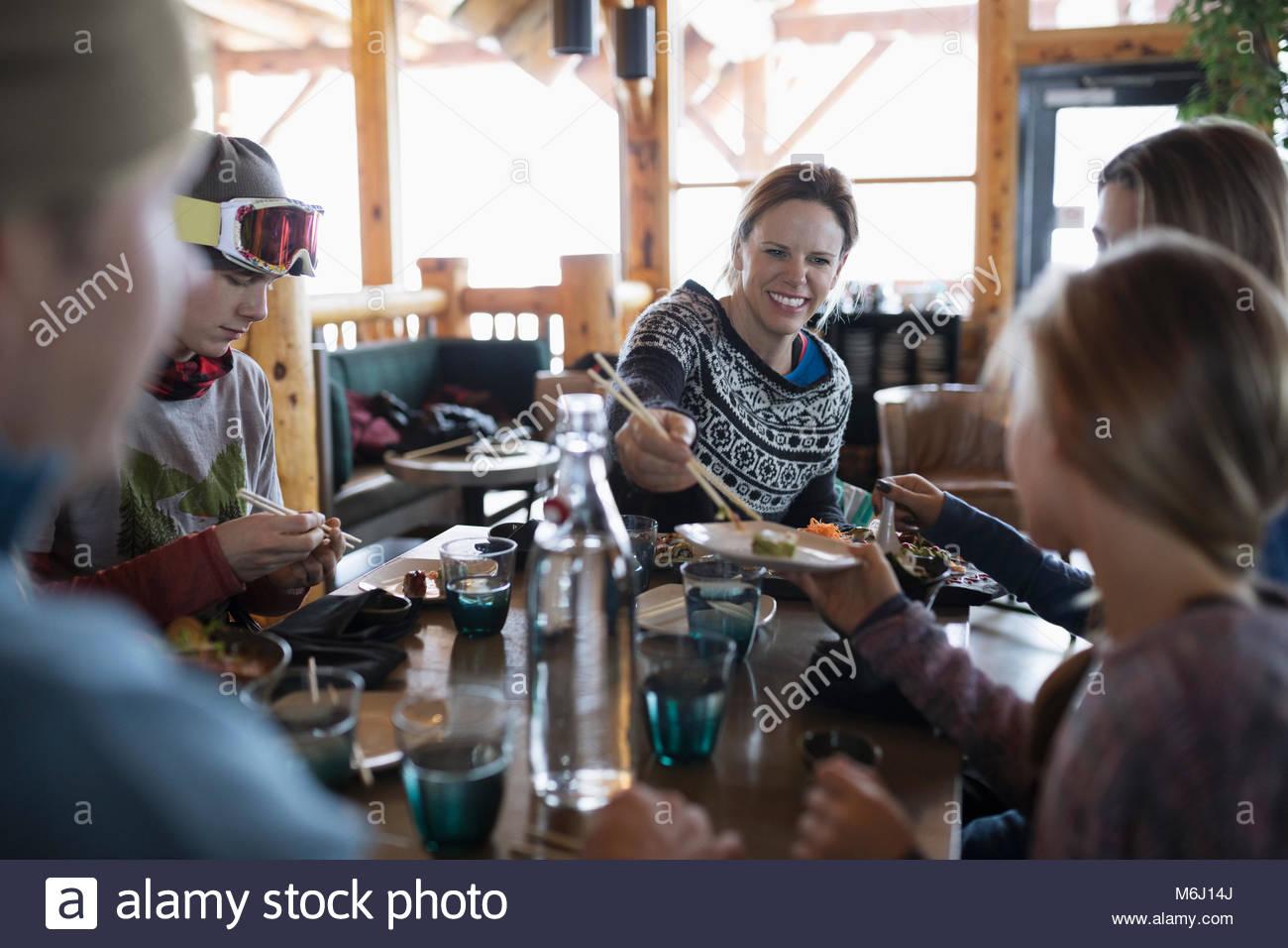 Gli sciatori in famiglia godendo il sushi al ski resort ristorante apres-ski Immagini Stock