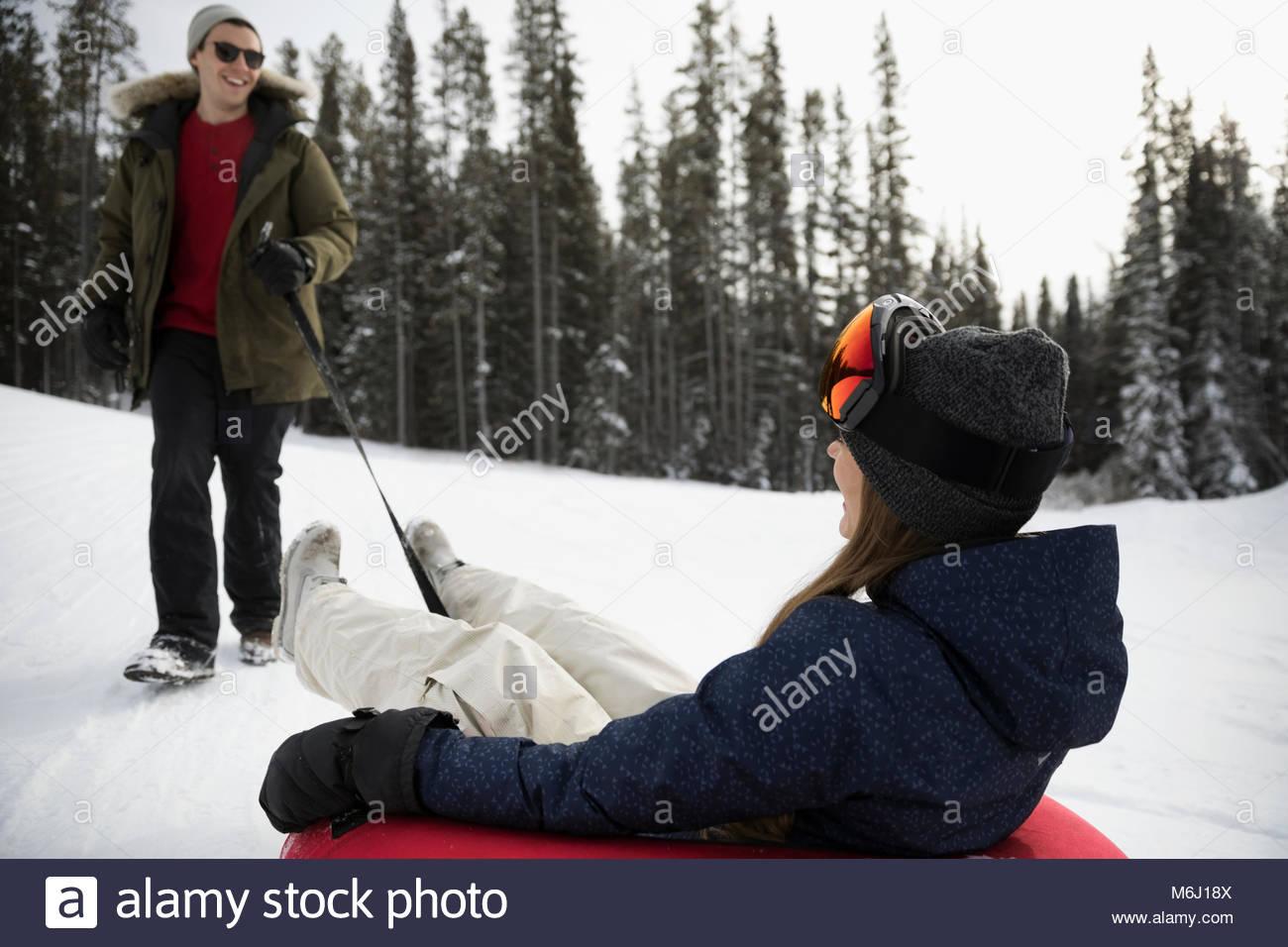 Ragazzo tirando fidanzata nel tubo interno nella neve Immagini Stock