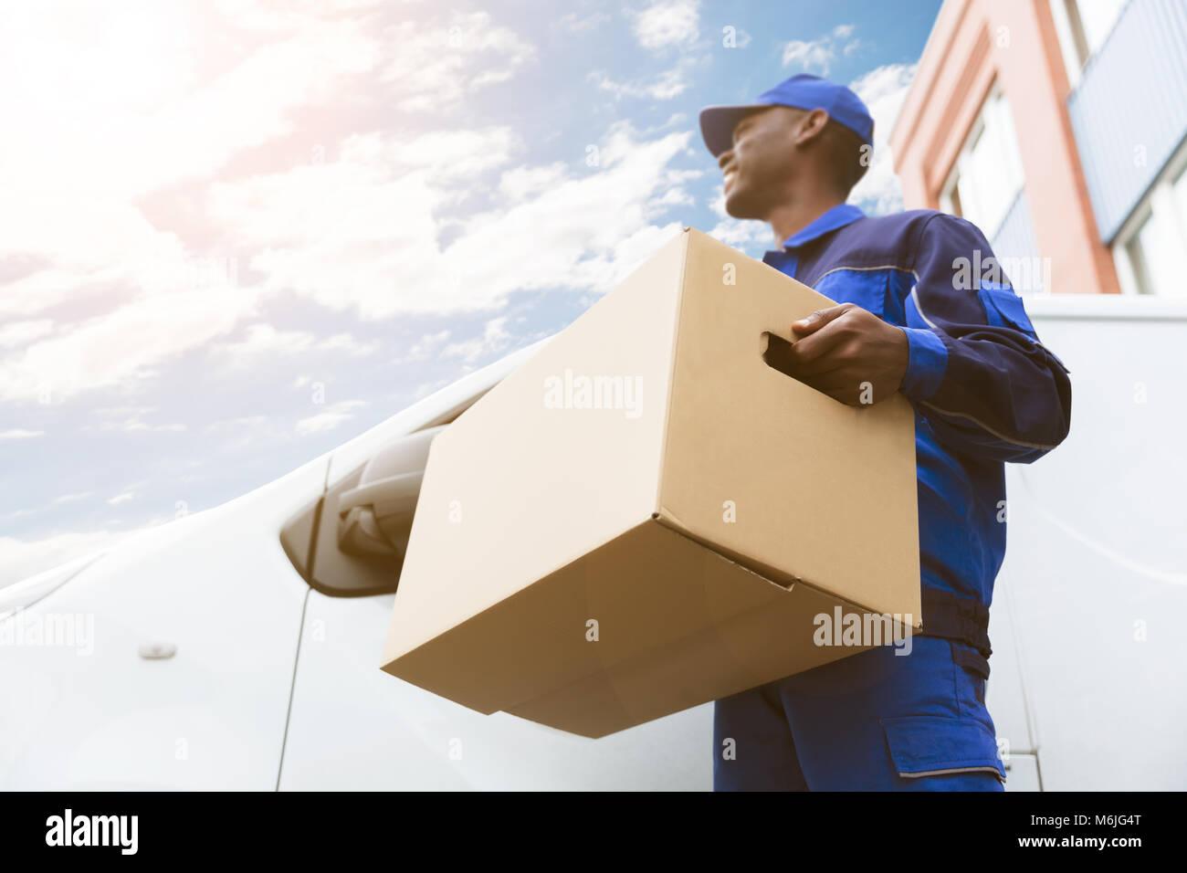 Basso Angolo di visione del caricatore uomo in piedi vicino al Van tenendo la scatola di cartone Immagini Stock