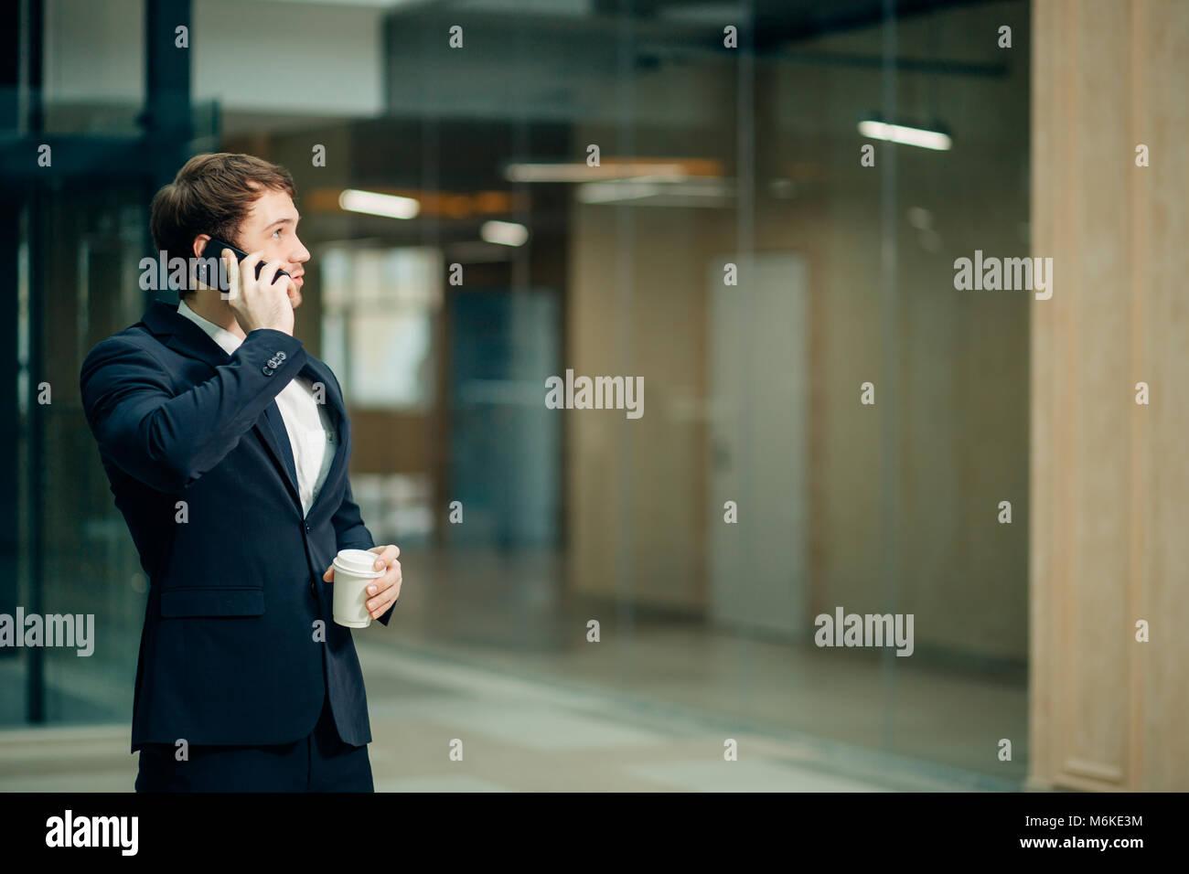Imprenditore in abito nero di parlare al telefono e a bere il caffè da asporto Immagini Stock