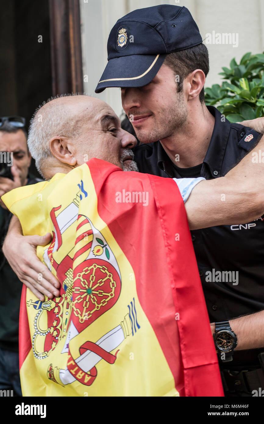 Manifestante por la unidad de España abraza una Onu policía nacional en la concentración por la unidad Immagini Stock