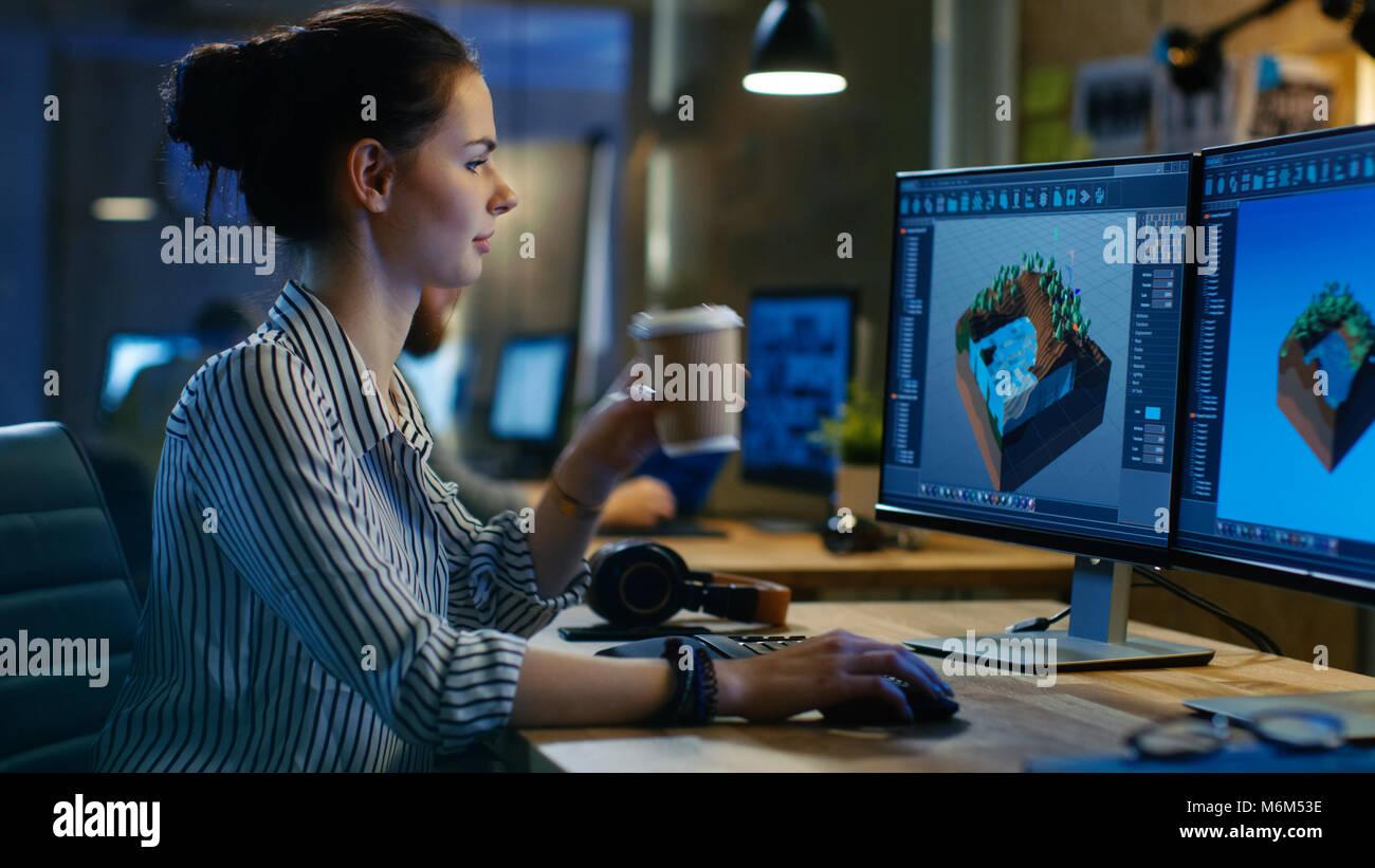Femmina dello sviluppatore del gioco funziona su un Design di livello sul Suo Personal Computer con due schermi, Immagini Stock
